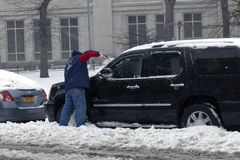 在雪风暴期间,人清洗汽车与刷子 库存图片
