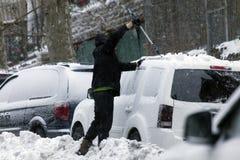在雪风暴期间,人清洗汽车与刷子 免版税图库摄影