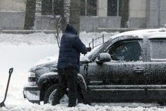 在雪风暴期间,人清洗汽车与刷子 免版税库存图片