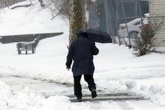 在雪风暴期间,人走与伞 免版税库存图片