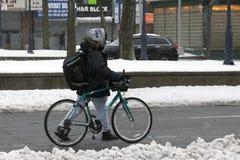 在雪风暴期间,人走与自行车 免版税库存照片