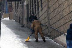 在雪风暴期间,人铲起街道 免版税库存图片