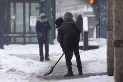 在雪风暴期间,人铲起雪 图库摄影