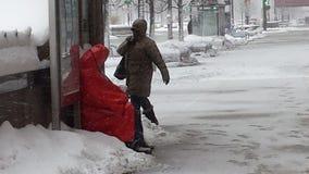 在雪风暴期间,无家可归的人发现了风雨棚在公共汽车站 免版税库存照片