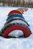 在雪,俄罗斯的明亮地色的轮胎行  免版税库存照片
