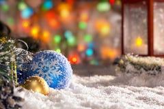 在雪,有一个蜡烛的,光诗歌选, bokeh一个红色灯笼的圣诞节球 免版税库存照片