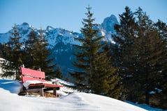 在雪,背景奥地利阿尔卑斯山的红色长凳 免版税库存图片