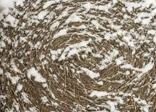 在雪,背景的圆的秸杆大包 免版税图库摄影