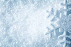 在雪,蓝色雪剥落水晶冬天背景的雪花 免版税库存照片