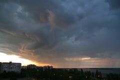 在雷和雨前的云彩在城市和河 图库摄影