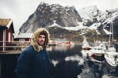 在雷讷村庄,挪威供以人员旅行家坐一个码头 免版税图库摄影