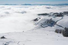 在雾围拢的山的上面的一个草甸在一好日子 免版税库存图片