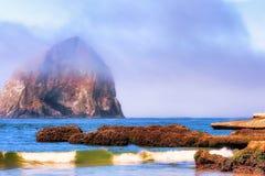 在雾的干草堆岩石在和平的城市 免版税图库摄影