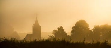 在雾的教会剪影 免版税库存图片
