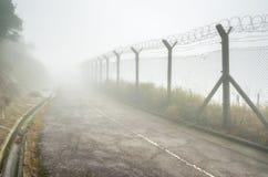 在雾的链子链接操刀和铁丝网 免版税库存照片