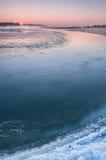 在雾盖的一条结冰的河的日出 免版税库存照片