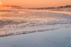 在雾盖的一条结冰的河的日出 库存照片