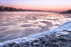 在雾盖的一条结冰的河的石河岸在黄昏期间 免版税库存照片