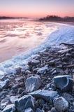 在雾盖的一条结冰的河的石河岸在黄昏期间 图库摄影