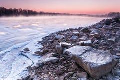 在雾盖的一条结冰的河的石河岸在黄昏期间 库存照片