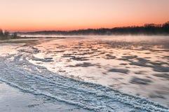 在雾盖的结冰的河在黄昏期间 图库摄影