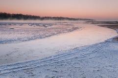 在雾盖的结冰的河在黄昏期间 免版税图库摄影