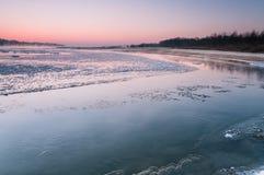 在雾盖的结冰的河在黄昏期间 库存照片