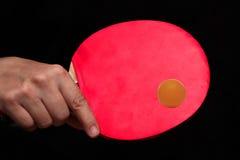 在震动手styleto的举行的反手击中了橙色乒乓球球 库存图片