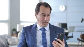 在震动的中间年迈的商人,当使用智能手机时 影视素材