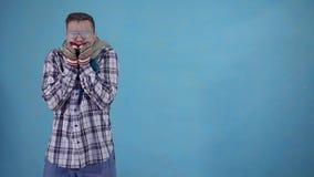 在霜和佩带的手套盖的结冰的人和在蓝色背景拷贝空间的一条围巾 股票录像