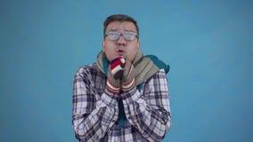 在霜和佩带的手套盖的结冰的人和在蓝色背景的一条围巾 股票视频