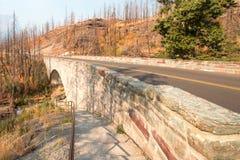 在露出小河的石桥梁在去太阳路在冰川国家公园在蒙大拿美国 免版税图库摄影