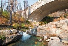 在露出小河的石桥梁在去太阳路在冰川国家公园在蒙大拿美国 免版税库存照片
