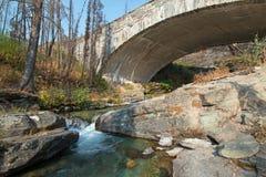 在露出小河的石桥梁在去太阳路在冰川国家公园在蒙大拿美国 图库摄影