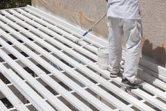 在露台盖子上上面的画家滚动的白色油漆  免版税库存图片