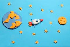 在露天场所,宇航员梦想的创造性的工艺彩色塑泥火箭 星、行星地球和月亮 动画片艺术 免版税库存照片