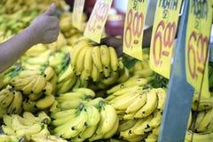 在露天市场摊位的消费者审查的香蕉 库存图片