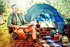 在露营地供以人员读在帐篷之外的地图 免版税库存照片