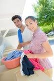 在露营地手洗涤的衣裳的夫妇 免版税库存图片
