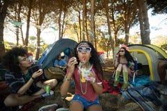 在露营地的少妇吹的泡影鞭子 免版税库存照片