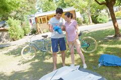 在露营地聚集的帐篷的夫妇 免版税库存照片