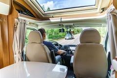 在露营者货车供以人员驾驶在一条路 图库摄影