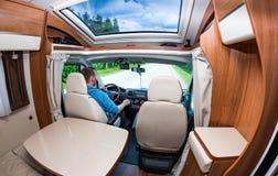 在露营者货车供以人员驾驶在一条路 免版税图库摄影
