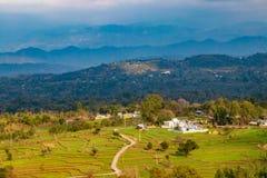 在青山和乡下房子顶部的农场 免版税图库摄影