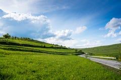 在青山春天,剧烈的天空蔚蓝的弯曲的柏油路 免版税库存图片