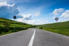 在青山春天,剧烈的天空蔚蓝的弯曲的柏油路 免版税库存照片
