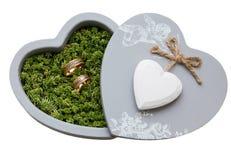 在青苔的婚戒,在以心脏的形式灰色箱子 免版税库存照片