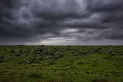 在青苔的黑暗的雨云报道了熔岩荒野 免版税图库摄影