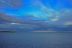 在青蓝色秋天天空中的橙色日落在灯塔附近的海在克里米亚 库存照片