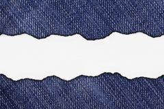 在靛蓝蓝色牛仔裤的裂口纸 库存照片